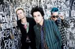 Members of the band Green Day standing by a graffiti-covered wall